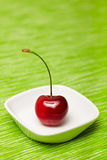 Single cherry in a bowl Royalty Free Stock Photography