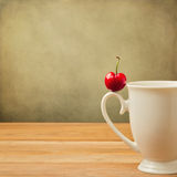 Single cherry on cup handle on grunge background Royalty Free Stock Images