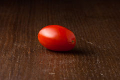 Single Cherry Tomato on wood table Royalty Free Stock Image