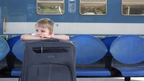 Single child with big luggage sit in train station, long waiting, good things stands to come. 4K stock video footage