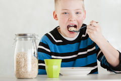 Single child feeding himself oatmeal Royalty Free Stock Photo
