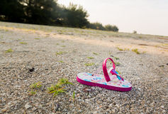 Single child flipflop on empty beach Royalty Free Stock Photography