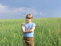 Single child under dark storm sky. Single child in a endless meadow under dark storm sky Stock Photography