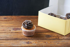 Single chocolate cup cake over paper box Royalty Free Stock Images