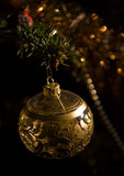 Single Christmas Ball. Beautiful single Christmas bauble hanging in a tree, with a dark background with some sparkles from the decoration Stock Photography