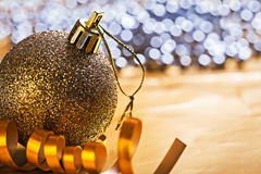 Single christmas ball and gold colored ribbon horizontal version Royalty Free Stock Image
