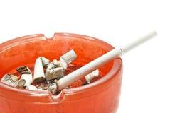 Single cigarette in glass ashtray Royalty Free Stock Photo