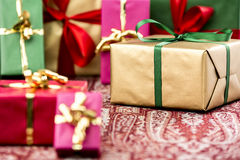 Single-Colored Presents for Many Occasions. Golden gift box with emerald bow amidst other presents in magenta, red, green and gold. Tightly-framed shot with Royalty Free Stock Photo