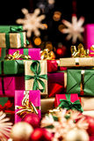 Single-Colored Xmas Gifts Stacked Up. Pile of plain Christmas presents between blurred baubles and straw stars. Vibrant colors. Magenta, gold, green and red Stock Photography