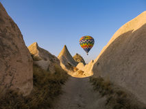 Hot air balloon floating above rock formations in Cappadocia Royalty Free Stock Photography