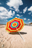 Single colourful umbrella sunny day Aberdovey Wales empty beach Stock Photo