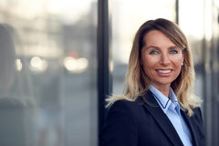 Single confident and attractive female businesswoman. In blue suit with grin leaning on window outdoors stock photos