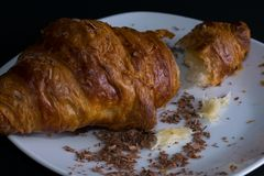 Single croissant on a white plate, dark background, side view. With chocolate chips and crumbs. Ready for breakfast Stock Image
