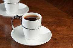 Single cup of hot, fresh coffee. Single white cup of hot, fresh, black coffee on old, wooden table Stock Photo