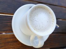 Single cup of latte. A single cup of latte coffee in a white cup and saucer on a grain surface Royalty Free Stock Photos