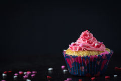 Single Cupcake and Pink Frosting with Scattered Sprinkles on Dark Background Royalty Free Stock Images