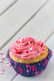 Single Cupcake and Pink Frosting on Table with Copy Space Above Vertical Stock Photos