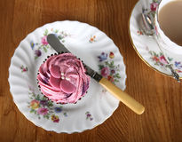 Single Cupcake with Tea. A single strawberry flavour cupcake with a cup of tea royalty free stock photos