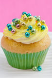 Single cupcake with yellow buttercream and colorful decorations, Stock Photo