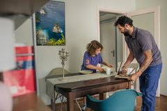 Father and young son setting their kitchen table for lunch stock image