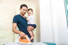 Single dad is ironing while carrying his son. People and Lifestyles concept. stock photography