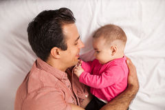 Single dad lying on a bed with his baby girl royalty free stock image