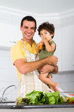 Single dad and son. Happy single dad holding toddler son in modern kitchen stock image