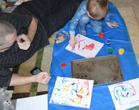 Single dad and son fingerpainting 1. Single father plays art critic while his son finger paints wild and crazy designs working on a mat on the living room floor stock photo