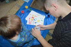 Single dad and son fingerpainting 3. Single father plays art critic while his son finger paints wild and crazy designs working on a mat on the living room floor royalty free stock photography