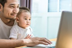 Single dad and son using laptop together happily. Technology and royalty free stock photography