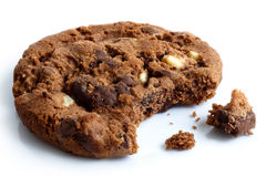 Single dark chocolate chip cookie, bite missing with crumbs, iso Royalty Free Stock Images
