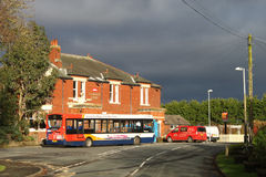 Single deck bus at stop outside village pub. Stock Photos