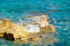 Single deck chair standing on a rock middle of the sea. Single chaise lounge standing on a rock middle of the sea horizontal Stock Image