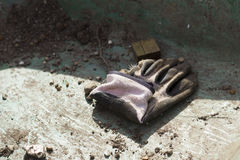 Single dirty well used gardening glove. End of the working day in the garden, mudded wheelbarrow base with a single well worn gardening glove Stock Photography