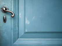 Single Door handle on old door. Painted with blue Royalty Free Stock Image