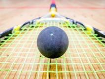 Single dot squash ball on racquet stings. Single dot squash ball on the racquet stings stock photo