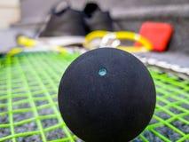 Single dot squash ball on racquet stings. Single dot squash ball on the racquet stings royalty free stock photography