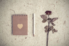 Single dried rose flower with notebook on mulberry paper Royalty Free Stock Photo
