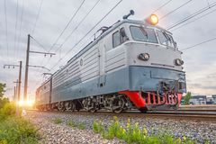 Single electric locomotive on the railway in the evening at sunset. stock photo