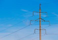 Single electric transmission tower. Concrete column. Against serene blue sky. Warm morning light stock images