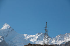 Single electricity pole snow mountain Royalty Free Stock Images