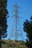 Single electricity transmission tower on a hill. Image shows a single, electricity power transmission tower and lines on a hill that has natural chaparral royalty free stock photography