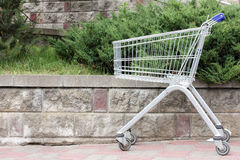 Single empty trolley. Empty shopping trolley stands in the street Stock Image