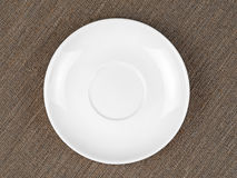 Single Empty White Plate on Coarse Fabric or Bagging. Background Royalty Free Stock Photography