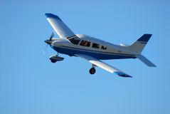Single engine airplane in flight. Against a clear blue sky Royalty Free Stock Image