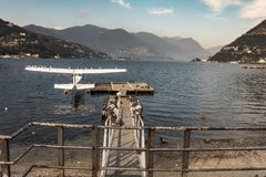 A single engine piston seaplane is moored at the pier. And occupied by birds sitting on the wings - lake Como stock photo
