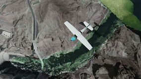 Single-engine plane and flying over dam at daylight stock footage