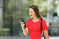 Entrepreneur in red reading a mobile phone in the street Royalty Free Stock Photos