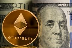 Single Ethereum coin in front of bank rolls of US currency Stock Photos