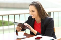 Executive working on line using a tablet in a bar Stock Image